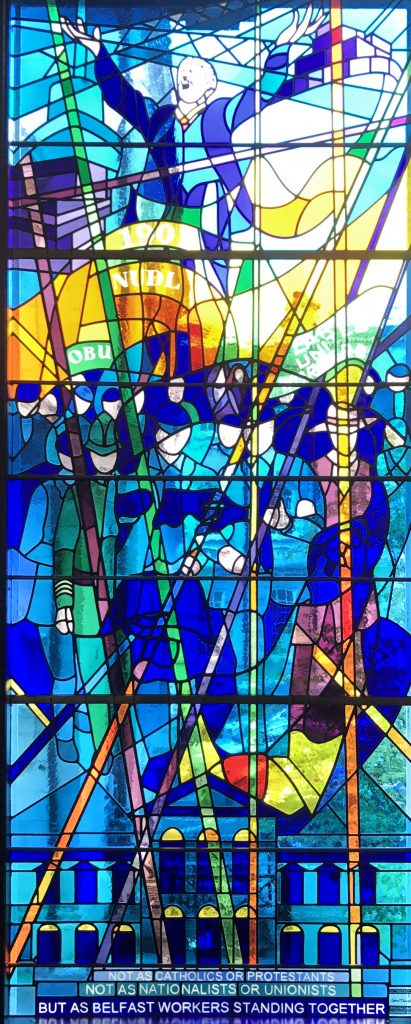 Stained glass window depicting striking workers bearing banners, with Jim Larkin speaking, arms outstretched