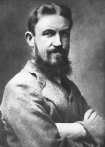 A portrait of a black-bearded George Bernard Shaw, from his right, with arms crossed.